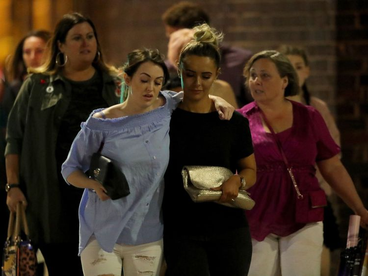Police escort members of the public from Manchester Arena after and explosion at Ariana Grande gig