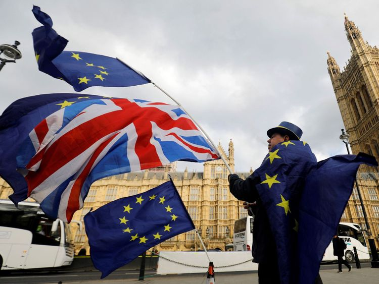An anti-Brexit demonstrator waves a Union flag alongside a European Union flag outside the Houses of Parliament