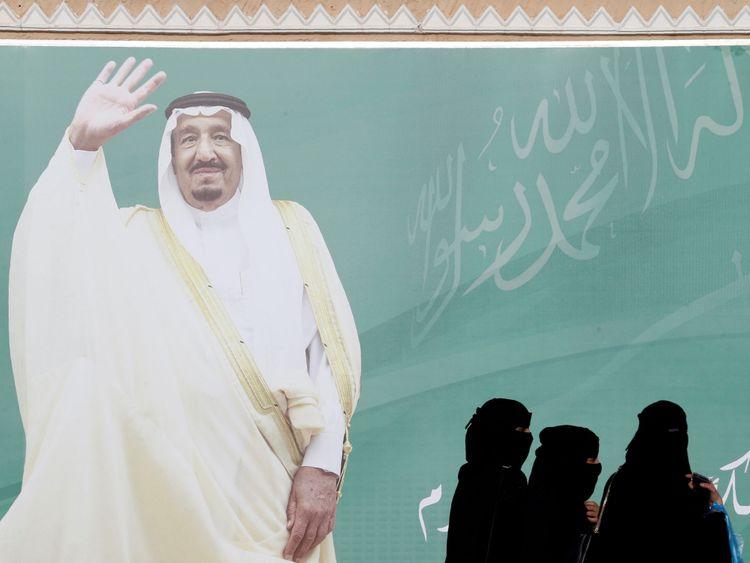 Women walk past a poster of Saudi Arabia's King Salman bin Abdulaziz Al Saud