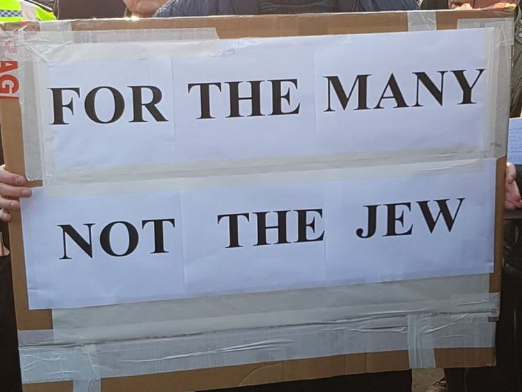 A campaigner holds a sign at an anti-Semitism protest outside Parliament